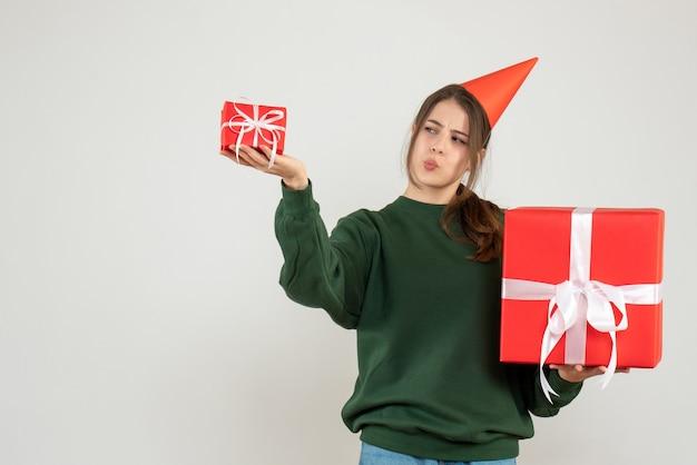 Vooraanzicht nieuwsgierig meisje met feestmuts die haar kerstcadeaus vergelijkt