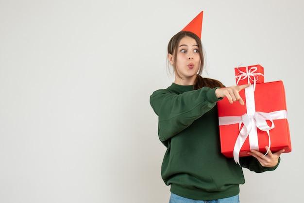 Vooraanzicht nieuwsgierig meisje met feestmuts die iets toont dat haar kerstcadeaus vasthoudt