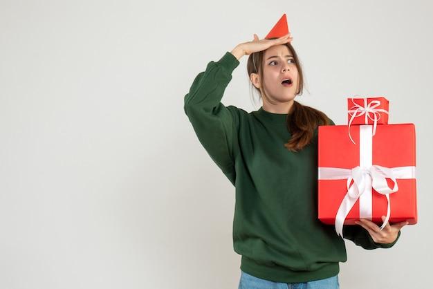 Vooraanzicht nieuwsgierig meisje met feestmuts observeren met haar kerstcadeaus