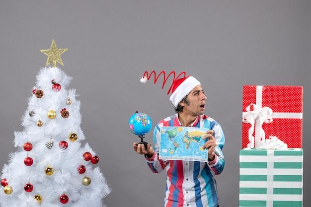 Vooraanzicht nieuwsgierige man met spiraalvormige lente kerstmuts kijken naar geschenken met wereldkaart en globe