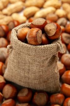 Vooraanzicht noten samenstelling verse hazelnoten en pinda's op witte bureaunoot snack pinda walnoot