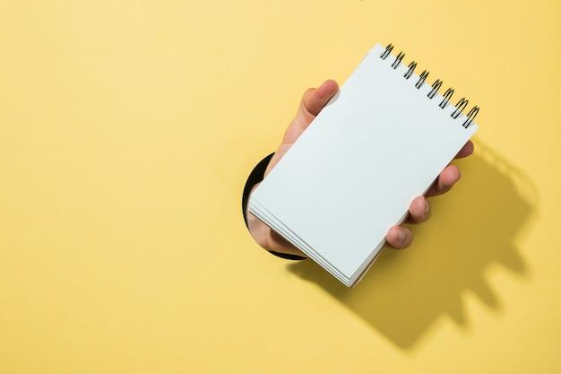 Vooraanzicht notitieboekje met gele achtergrond
