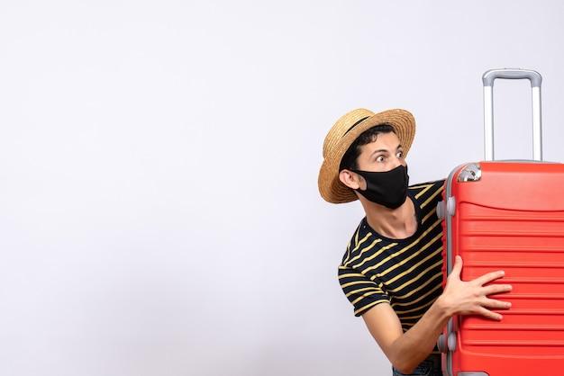 Vooraanzicht ongerust gemaakte jonge toerist met zwart masker dat zich achter rode koffer verstopt