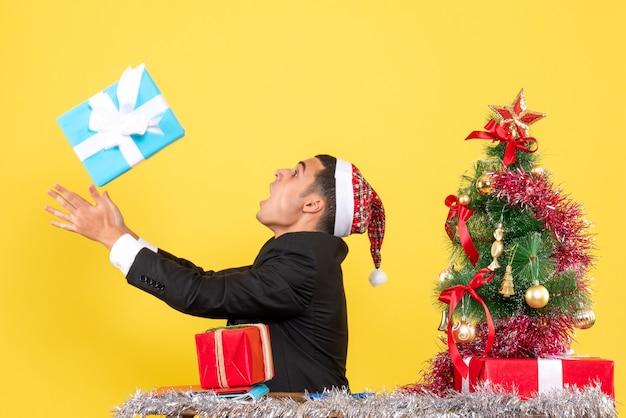 Vooraanzicht oonfused man met kerstmuts zittend aan de tafel proberen zijn huidige kerstboom en geschenken te vangen