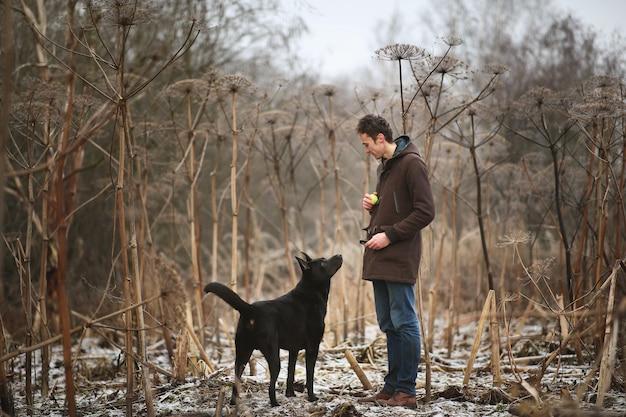 Vooraanzicht op een jonge stijlvolle blanke man training met grote zwarte hond in de buitenlucht