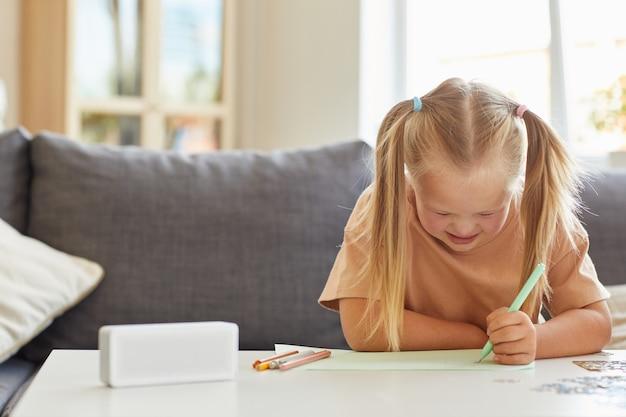 Vooraanzicht op schattig klein meisje met het syndroom van down, afbeeldingen tekenen tijdens ontwikkelingslessen thuis, kopie ruimte