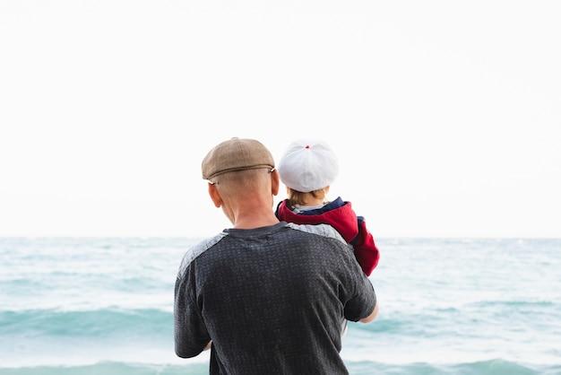 Vooraanzicht opa en kleinzoon aan zee