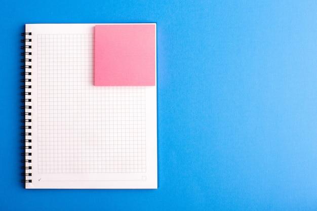 Vooraanzicht open voorbeeldenboek met roze sticker op het blauwe bureau
