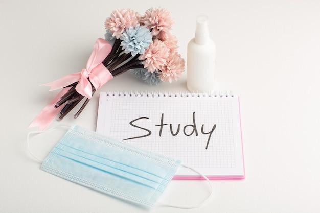 Vooraanzicht open voorbeeldenboek met spuitmasker en bloemen op wit oppervlak