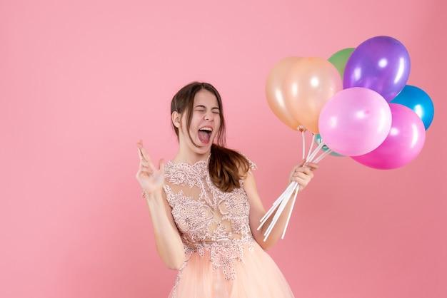Vooraanzicht opgetogen feestmeisje met feestmuts met ballonnen geluk maken teken