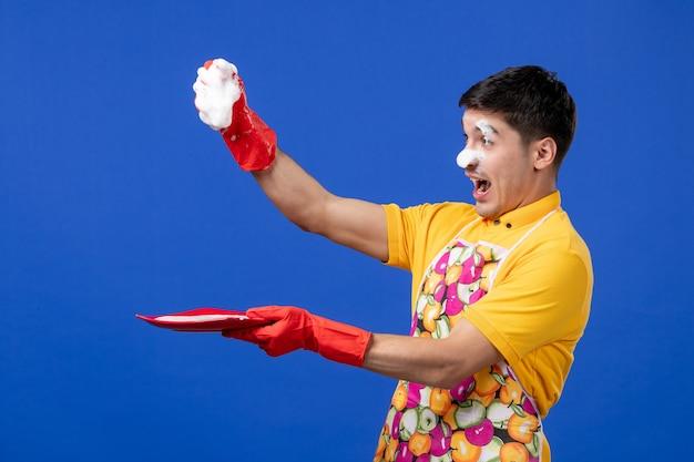 Vooraanzicht opgetogen huishoudster met schuim op zijn gezicht knijp spons op blauwe ruimte