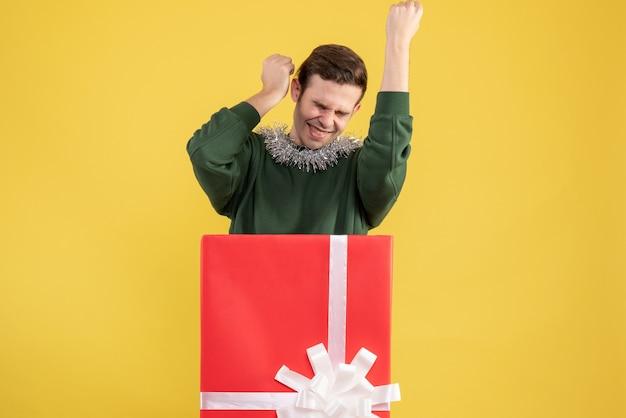 Vooraanzicht opgetogen jonge man met winnend gebaar achter grote geschenkdoos op geel