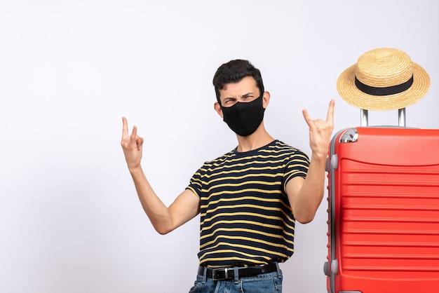 Vooraanzicht opgetogen jonge toerist met zwart masker dat zich dichtbij rode koffer bevindt die rock n roll-teken toont