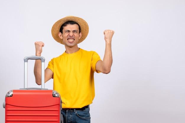 Vooraanzicht opgetogen jongeman met geel t-shirt en strooien hoed Gratis Foto