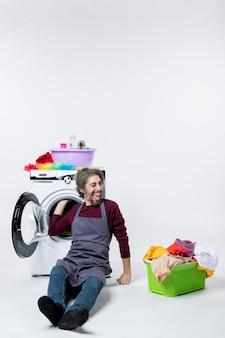 Vooraanzicht opgetogen mannelijke huishoudster die de wasmand van de wasmachine inlevert op een witte achtergrond
