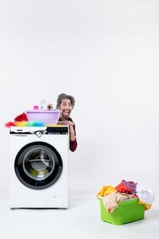 Vooraanzicht opgetogen mannelijke huishoudster in schort zittend achter wasmachine wasmand op witte achtergrond