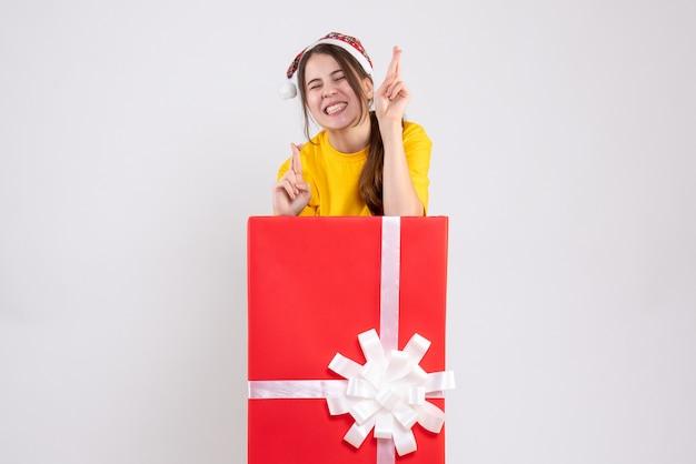 Vooraanzicht opgetogen meisje dat met santahoed goed geluksteken maakt dat zich achter grote kerstmisgift bevindt
