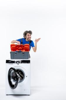 Vooraanzicht opgetogen reparateur die gereedschapstas opent, wijzend in de juiste richting achter de wasmachine op witruimte