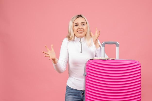 Vooraanzicht opgewonden jonge dame die zich achter roze koffer bevindt