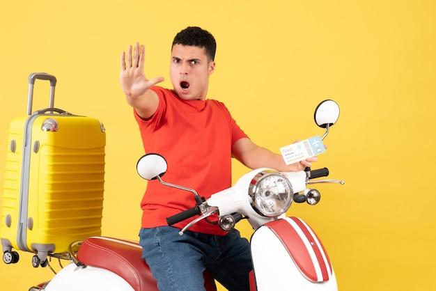 Vooraanzicht opgewonden jonge man op bromfiets bedrijf kaartje stopbord maken