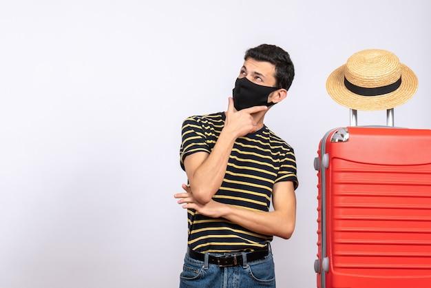 Vooraanzicht opgewonden jonge toerist met zwart masker dat zich dichtbij rode koffer bevindt