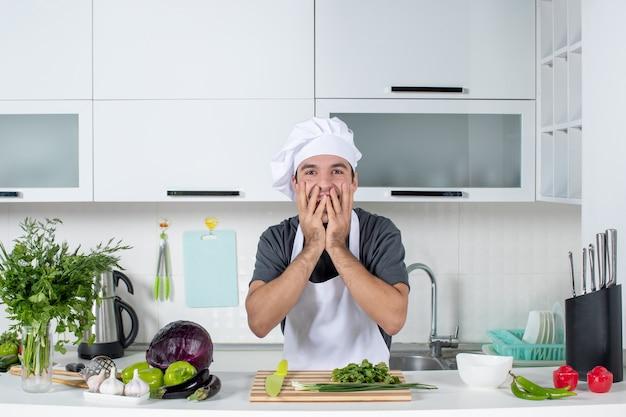 Vooraanzicht opgewonden knappe mannelijke kok in uniform staande achter de keukentafel