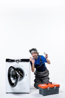 Vooraanzicht opgewonden reparateur met stethoscoop zittend in de buurt van wasmachine op witruimte