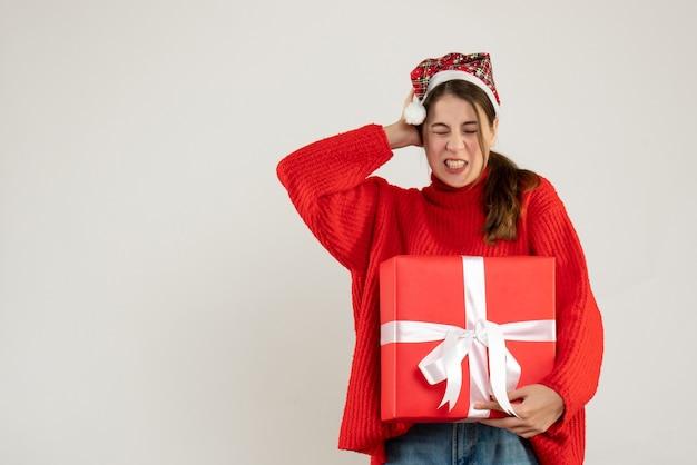 Vooraanzicht opgewonden schattig meisje met kerstmuts bedrijf aanwezig die haar oor status behandelt