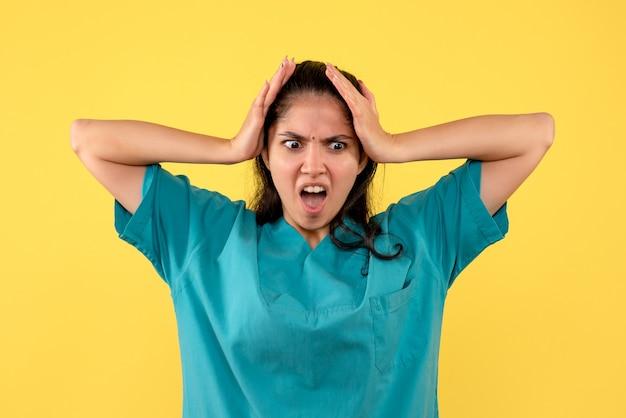 Vooraanzicht opgewonden vrouwelijke arts die zich op gele achtergrond bevindt