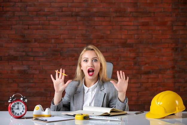 Vooraanzicht opgewonden vrouwelijke ingenieur die achter haar werkplek zit