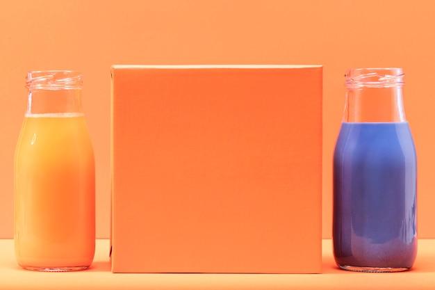 Vooraanzicht oranje en blauwe smoothies met blanco oranje vierkant