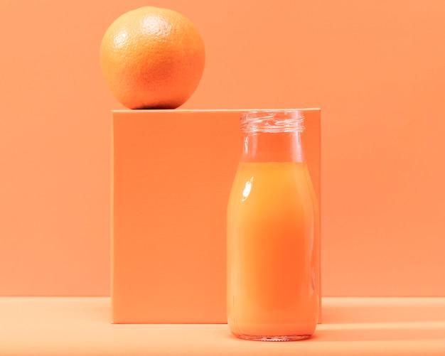 Vooraanzicht oranje en smoothie in fles
