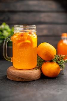 Vooraanzicht oranje limonade in glas op houten plank sinaasappels op bruin geïsoleerd oppervlak