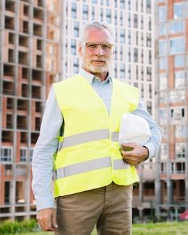 Vooraanzicht oude architect met vest en helm