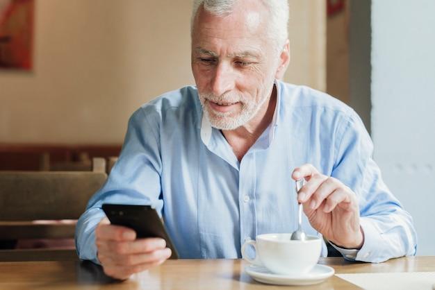Vooraanzicht oude man kijkend naar zijn telefoon