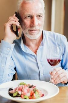 Vooraanzicht oude man praten over zijn telefoon