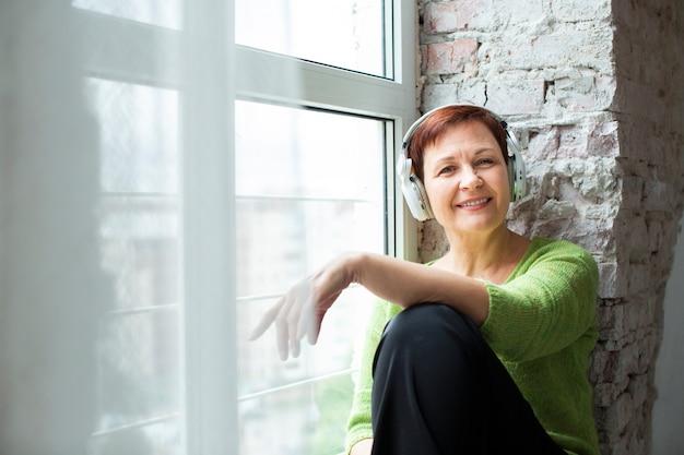 Vooraanzicht ouderling bij raam luisteren muziek