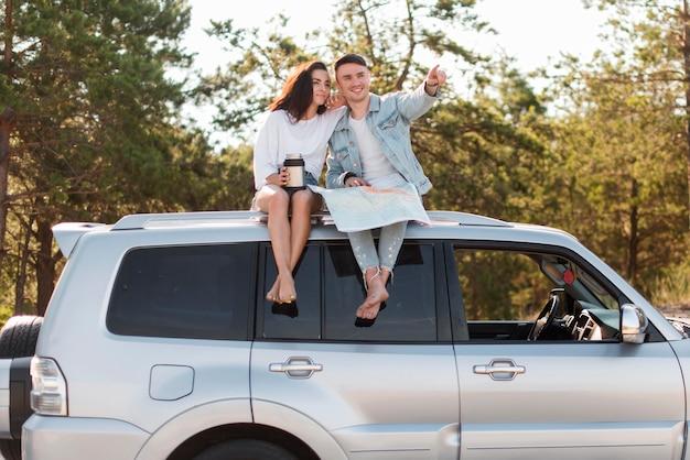 Vooraanzicht paar zittend op auto