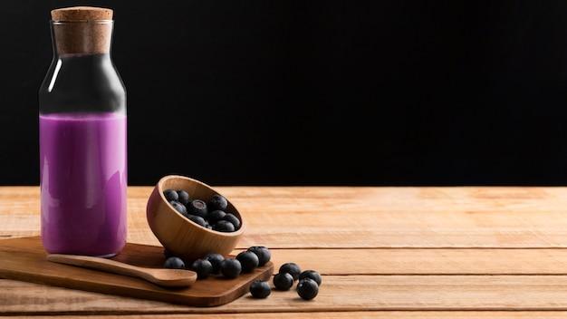 Vooraanzicht paarse smoothie en bosbessen met kopie-ruimte
