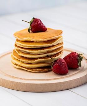 Vooraanzicht pannenkoeken met aardbeien op een dienblad