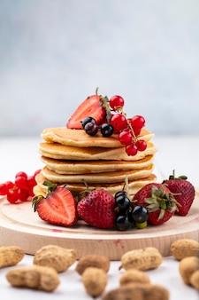 Vooraanzicht pannenkoeken met aardbeien zwarte en rode aalbessen op een dienblad met pinda's