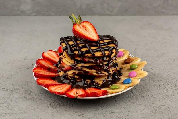 Vooraanzicht pannenkoeken met gesneden rode aardbeien en bananen samen met chocolade binnen plaat op de lichte vloer
