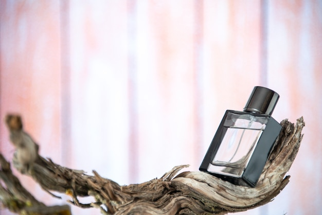 Vooraanzicht parfumfles op gedroogde boomtak geïsoleerd op naakte achtergrond vrije ruimte