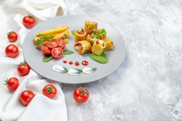 Vooraanzicht plantaardige patérolletjes met tomaten en frietjes in plaat op wit oppervlak