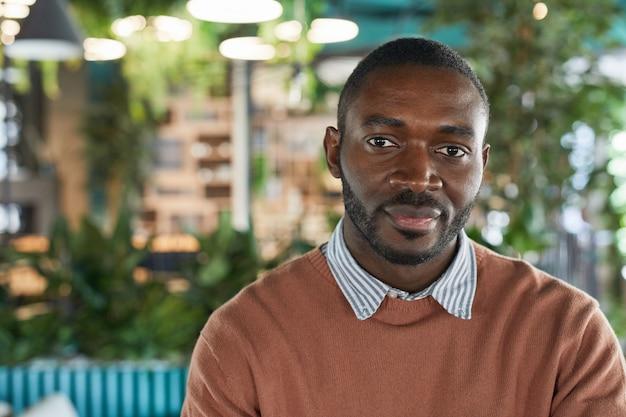 Vooraanzicht portret van afro-amerikaanse man die naar de camera kijkt terwijl hij poseert in een milieuvriendelijk café-interieur versierd met verse groene planten, kopieer ruimte