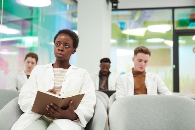 Vooraanzicht portret van een jonge afro-amerikaanse vrouw die een laboratoriumjas draagt terwijl ze in het publiek zit en luistert naar een lezing over medicijnen op de universiteit of een coworkingcentrum, kopieer ruimte