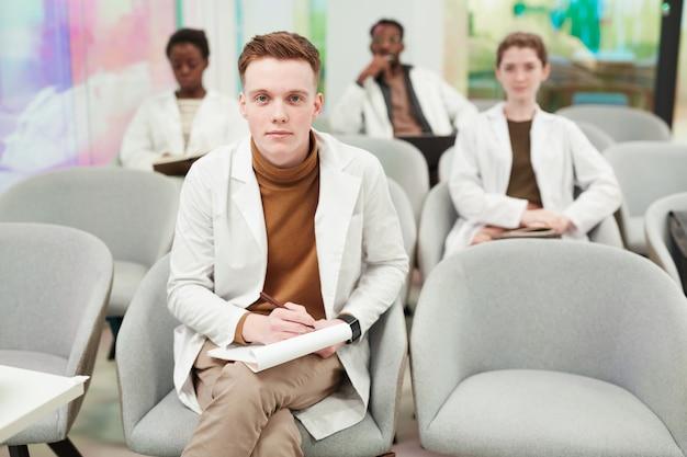 Vooraanzicht portret van een jonge man die naar de camera kijkt terwijl hij in het publiek zit en luistert naar een lezing over medicijnen op de universiteit of een coworkingcentrum, kopieer ruimte