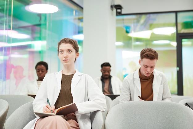 Vooraanzicht portret van een jonge vrouw die een laboratoriumjas draagt terwijl ze in het publiek zit en luistert naar een lezing over medicijnen op de universiteit of een coworkingcentrum, kopieer ruimte