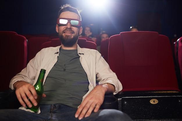 Vooraanzicht portret van lachende bebaarde man met stereoglazen tijdens het kijken naar 3d-film in bioscoop, kopieer ruimte