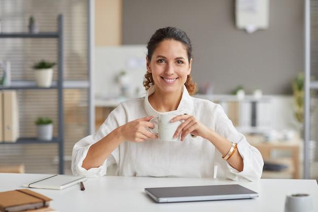 Vooraanzicht portret van lachende jonge vrouw met koffiemok zittend op de werkplek en glimlachend in de camera, kopieer ruimte